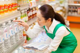 スーパーマーケットの商品在庫管理をする女性従業員の写真素材 [FYI01396385]