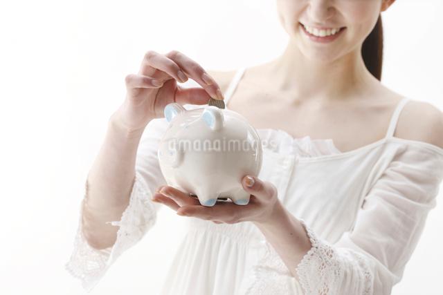 貯金箱にコインを入れている女性の写真素材 [FYI01396926]