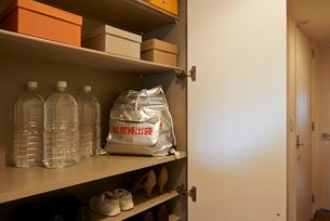 玄関の棚に置かれた備蓄用の水と非常用避難リュックの写真素材 [FYI01398515]