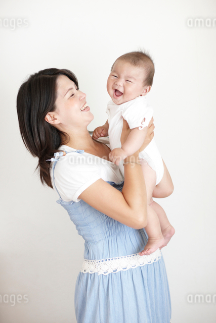 お母さんに抱っこをされて喜ぶ笑顔の赤ちゃんの写真素材 [FYI01399121]