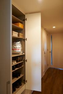 玄関の棚に置かれた備蓄用の水と非常用避難リュックの写真素材 [FYI01399148]