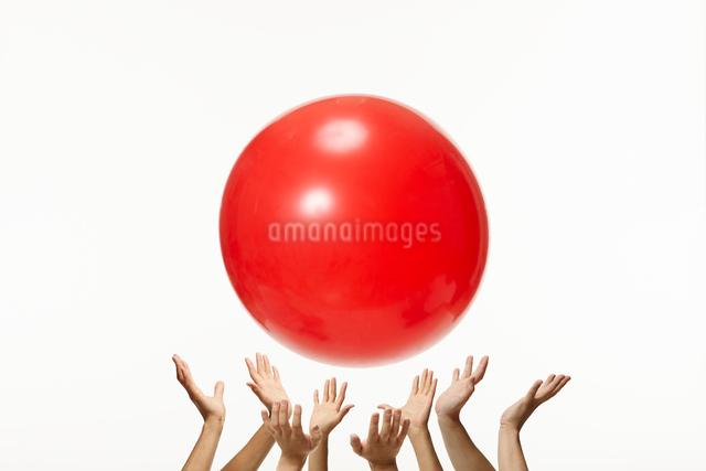 沢山の手が大きな赤いボールを飛ばすの写真素材 [FYI01399169]