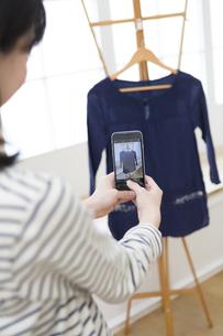 服を撮影する女性の写真素材 [FYI01399462]