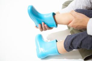 水色の長靴を履かせてもらう子どもの足の写真素材 [FYI01399736]