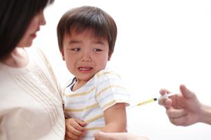 注射を打たれる子どもを抱く母親と医者の写真素材 [FYI01401113]