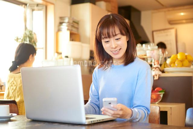 カフェにてパソコンと仕事をする女性の写真素材 [FYI01403239]