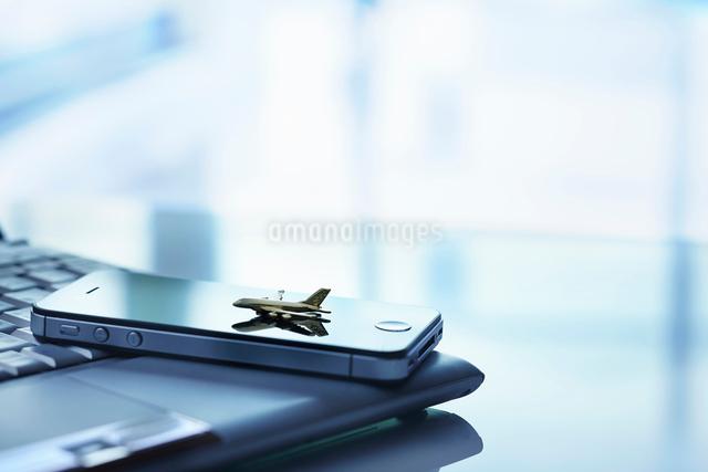 パソコンの上の置かれたスマートフォンと飛行機の写真素材 [FYI01403861]
