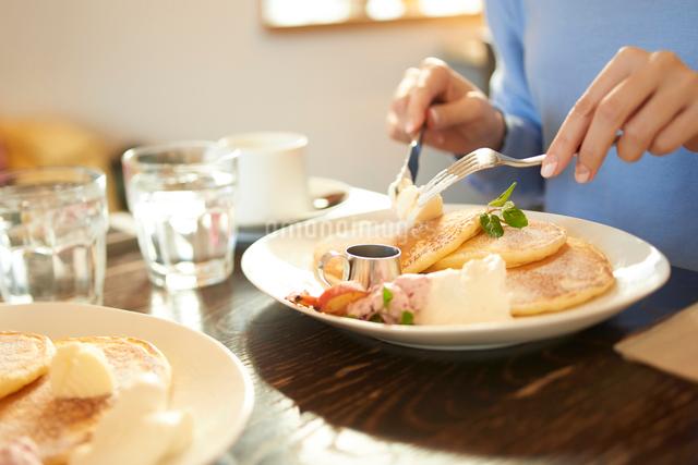 カフェにて友人とパンケーキを食べる女性の写真素材 [FYI01403985]