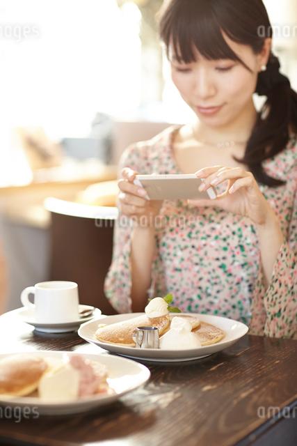 カフェにてパンケーキを携帯電話で撮影する女性の写真素材 [FYI01404150]