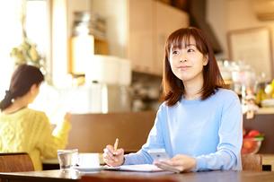 カフェで携帯電話を見ながらスケジュール帳を確認する女性の写真素材 [FYI01404254]