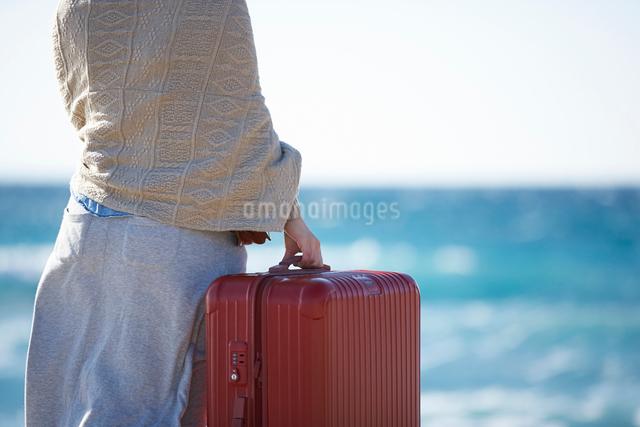 海を眺めるスーツケースを持った女性の写真素材 [FYI01405152]