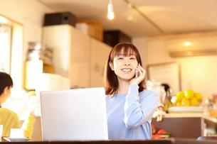 カフェにて電話をする女性の写真素材 [FYI01406417]