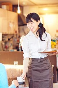 カフェにて接客をして働く女性の写真素材 [FYI01406703]