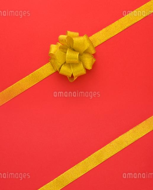 ゴールドのリボン/赤バックの写真素材 [FYI01409389]