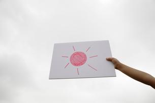太陽の絵を掲げる子供の手の写真素材 [FYI01409893]