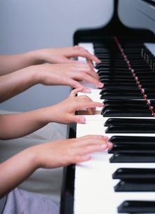 ピアノをひく女の子とお母さんの手の写真素材 [FYI01410048]