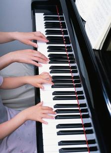 ピアノをひく女の子とお母さんの手の写真素材 [FYI01410112]