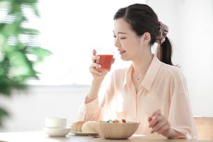 朝食のトマトジュースを持つ若い女性の写真素材 [FYI01410437]