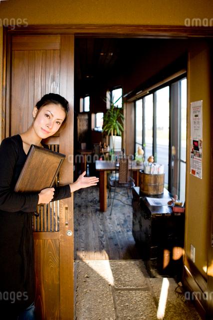 喫茶店に誘導するウエイトレスの写真素材 [FYI01410627]