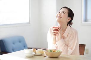 朝食のトマトジュースを持つ若い女性の写真素材 [FYI01410694]