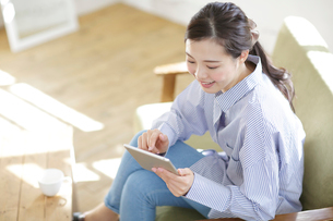 ソファーでタブレットPCをやっている若い女性の写真素材 [FYI01411038]