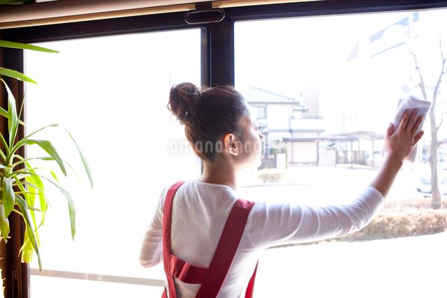 窓を拭く20代日本人女性の写真素材 [FYI01412049]