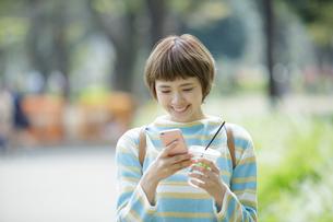 公園でスマホをする若い女性の写真素材 [FYI01412686]
