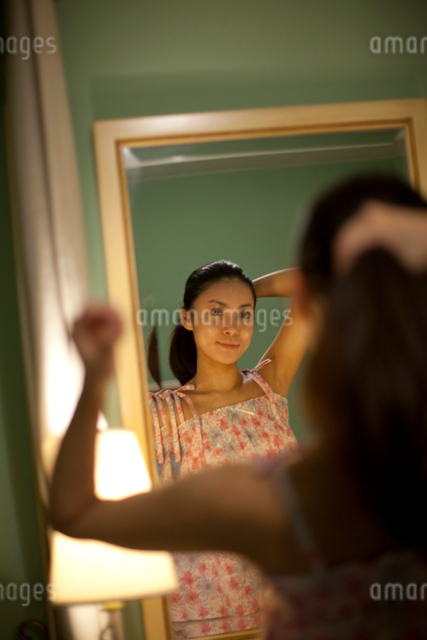 鏡の前で髪の毛を直す若い女性の写真素材 [FYI01412950]