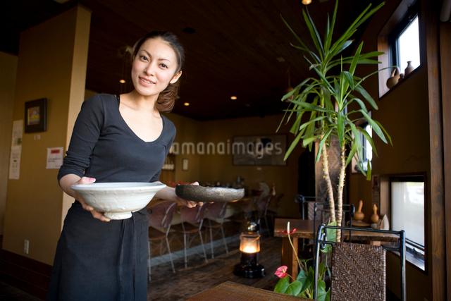 料理を運ぶウエイトレスの写真素材 [FYI01413027]
