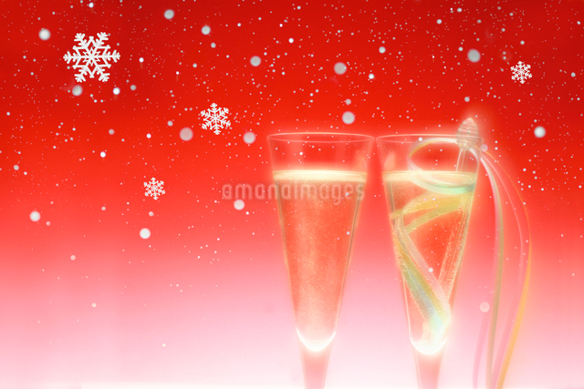 シャンパングラスと雪(赤バック)の写真素材 [FYI01413803]