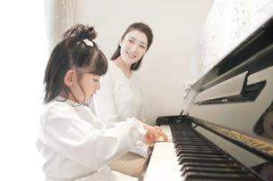ピアノを弾く娘と見守る母親の写真素材 [FYI01414084]