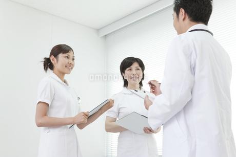 医師と打合せする2人の看護師の写真素材 [FYI01414112]