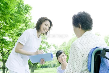 話をするシニア女性と看護師とヘルパーの写真素材 [FYI01414502]