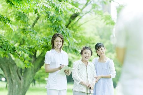 芝生の上に立つシニア女性と看護師とヘルパーの写真素材 [FYI01414566]