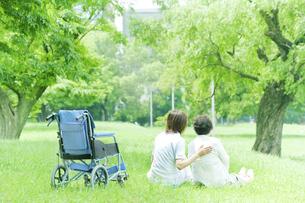 芝生に座るシニア女性と看護師の後ろ姿の写真素材 [FYI01414674]
