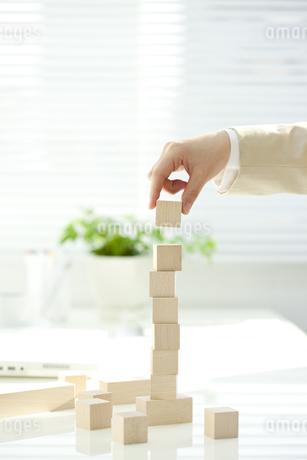 オフィスで積み木を積み上げる女性イメージの写真素材 [FYI01414914]