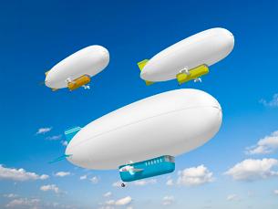 大空をゆっくり飛ぶ三機の白い飛行船のイラスト素材 [FYI01415341]