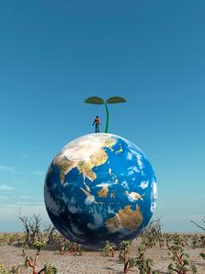 芽が出た地球に乗って佇む一人の男のイラスト素材 [FYI01415435]