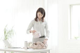 バッグにお弁当を入れる女性の写真素材 [FYI01415636]