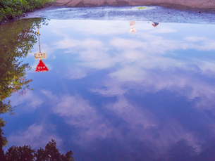 冠水した道路の水たまりに映る晴れ間の写真素材 [FYI01417346]