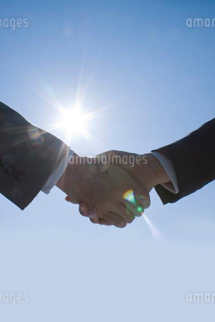太陽の下で握手をする手の写真素材 [FYI01417513]