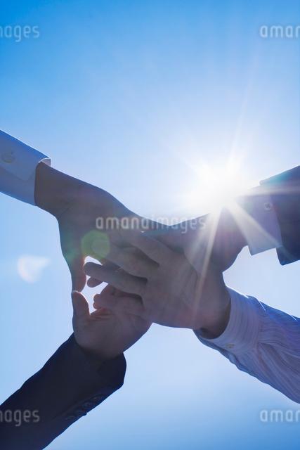 青空の中で円陣を組む4つの手の写真素材 [FYI01417606]