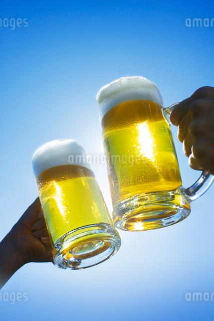 青空の中でジョッキビールで乾杯の写真素材 [FYI01417617]