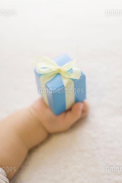 プレゼントを持つ赤ちゃんの手の写真素材 [FYI01417751]