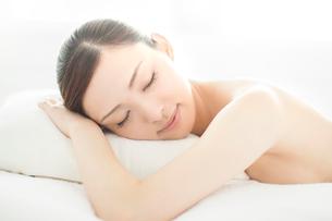 ベッドにうつ伏せになり目を閉じる女性の写真素材 [FYI01417780]