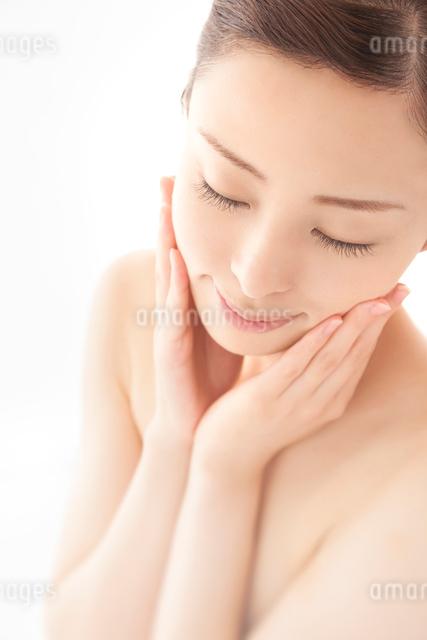 両手を頬にあてて目を閉じ微笑む女性の写真素材 [FYI01417886]