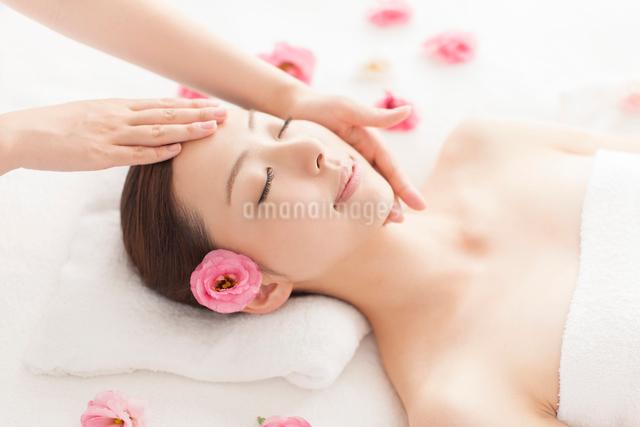 耳元に花を挿しベッドに仰向けで顔にマッサージを受ける女性の写真素材 [FYI01417913]