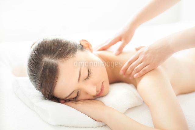 ベッドにうつ伏せで肩にマッサージを受ける女性の写真素材 [FYI01418028]