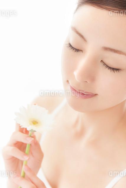 白いガーベラを手に目を閉じる女性の写真素材 [FYI01418161]