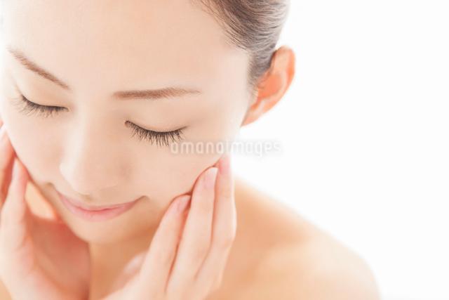 目を閉じ頬に両手を寄せる女性の写真素材 [FYI01418189]